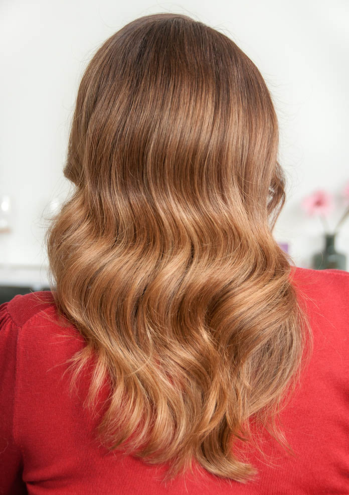 Woman with long dark hair and wave hairstyle in beauty salon