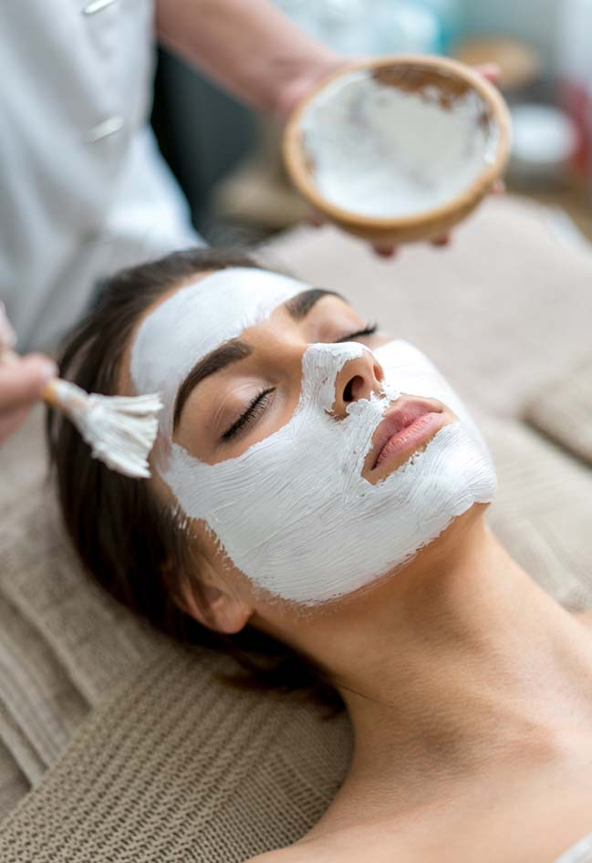Beauty portrait of a woman getting a facial at the spa and relaxing - skincare concepts