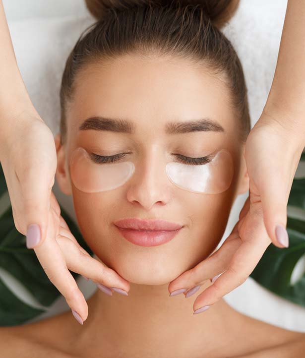 Woman with eye patches having face massage at beauty salon