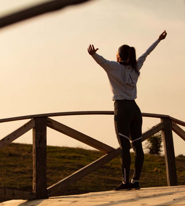 Rear view of athletic woman with arms outstretched standing on a bridge and enjoying in freedom at dawn.